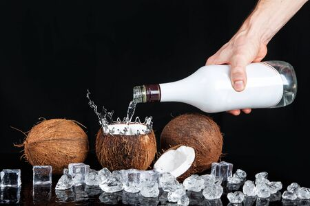 tropical coconut with ice and splashing water on black background