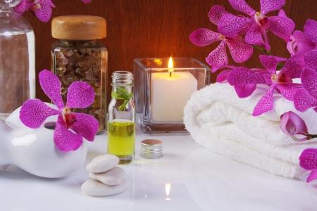 Wellnessbereich mit lila Orchidee, äth. Öl, Salz, Handtuch, weißem Stein und brennender Kerze