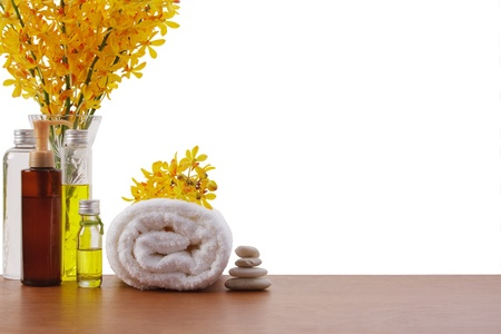 yellow orchid, towel roll, massage oil bottles, balance stone with copy space photo