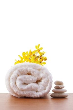 towel roll setting with yellow orchid and balance stone on white copy space Stock Photo