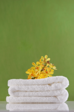 yellow orchid and towel on green backgrounds