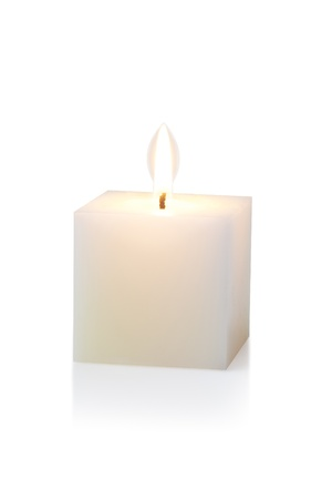 white candle: burning white cubic candle, on white