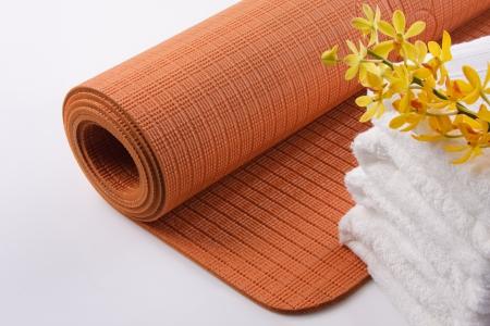 Yoga Mat mit Handtuch und Orchideen Standard-Bild