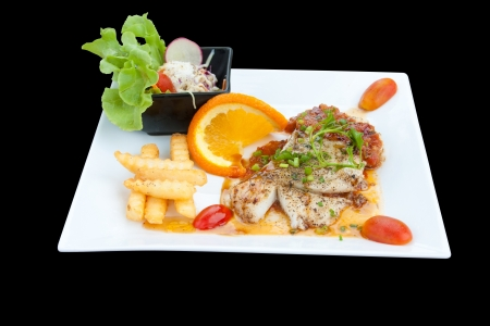fish steak with fries and salad on white plate isolated black photo