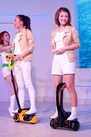 Bangkok - JANUARY  10 : two pretty young women present Whee, the new segway in small size by toyota. It is ridden in a standing position. Those are exhibit on January 5 - 22 in toyota pavillion in BOI 2011 at Muang Thong Thani, Bangkok