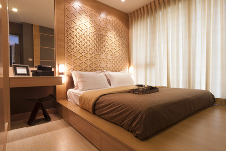 luxury hotel room: bedroom decorated with wood and warm light.