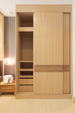 wooden furniture: sliding doors wardrobe furnishing in small room.