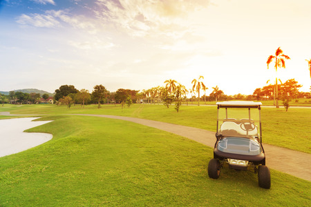 private club: golf car with sun set in golf course.