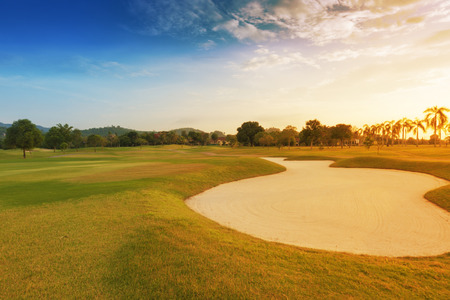 fairway: sand trap in golf course with sun set.