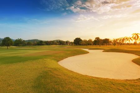 Sandfang auf einem Golfplatz mit Sonnenuntergang.