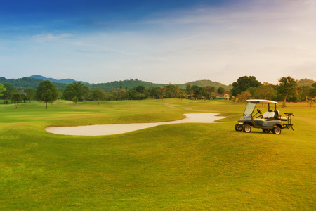 golf course with sand trap and golf car.