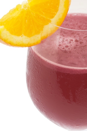 mocktail: closeup red mocktail in wine glass with orange on white. Stock Photo