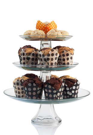 stand teapot: cupcakes and scones with three tiered tray isolated on white. Stock Photo