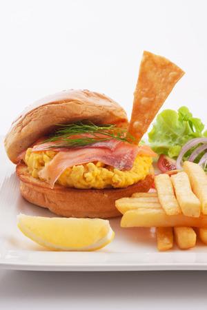 scrambled eggs: hamburguesa de salmón ahumado y huevos revueltos servido con francés fritos.