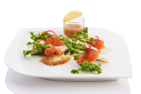 raw salmon and radish sprout roll fill with spicy sauce in plate isolated on white. photo