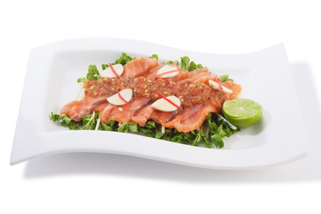 raw salmon and radish sprout fill with spicy sauce in plate isolated on white. photo