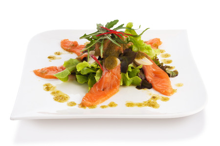 salmon salad with spicy sauce in plate isolated on white. photo