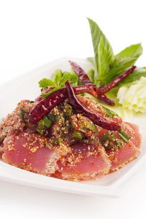 Spicy fresh tuna tataki thai style with vegetable on white.