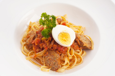 chilli sauce: spaghetti with chilli sauce, grilled sausage named sai-aue and boiled egg on white.