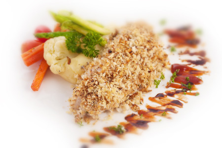 breadcrumbs: grilled fish sprinkled with breadcrumbs on white.