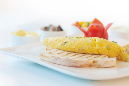 hashbrown: Omelette or scrambled egg served with hash-brown and tomato, on white.