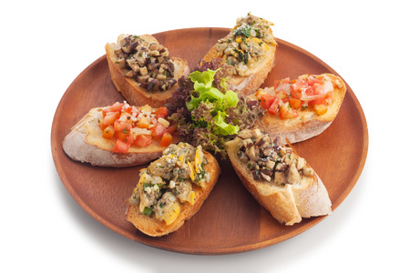 medley: Medley bruschetta topping with sauteed mushroom garlic butter clam tomato salsa on wood plate, isolated on white.