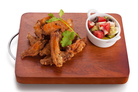 tabasco: Fried chicken wing marinated with tabasco sauce served with greek salad, isolated on white.