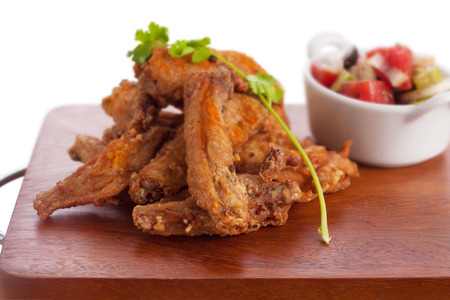 carte: Fried chicken wing marinated with tabasco sauce served with greek salad. Stock Photo