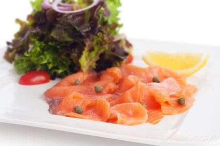 salmon ahumado: Salmón ahumado con ensalada asiática mezcla, la cebolla y aderezo balsámico, en blanco. Foto de archivo