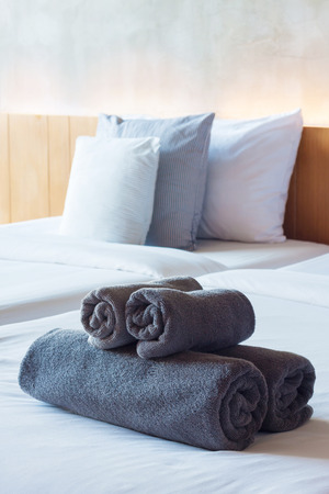 Towels roll on bed in modern hotel room. Stock Photo