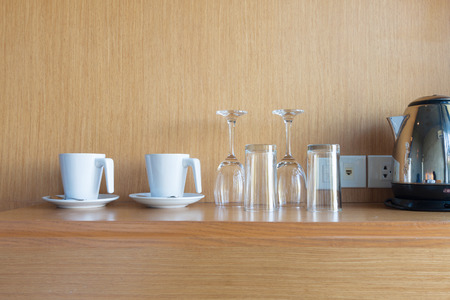 prepared cup and glass on wood shelf in luxury hotel room. Stock Photo