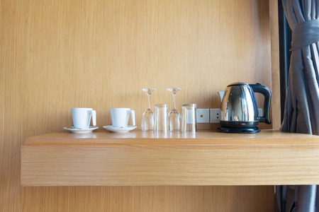 room decoration: prepared cup , glass and electric kettle on wood shelf in luxury hotel room.