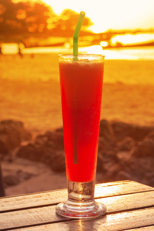 Watermelon smoothie on table with warm sunset sky and sea view of Lanta Island-Krabi-Thailand.