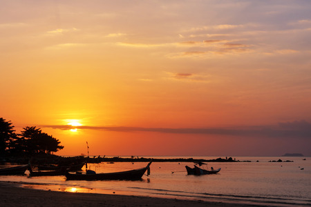 Sunset sky and fishing boats on beach at Lanta island, Krabi, Thailand.