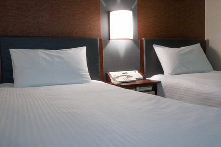 bedside: twin bed hotel room with bedside control. Stock Photo