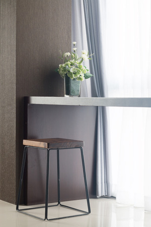 modern chair: long table near window with vase and chair. Stock Photo