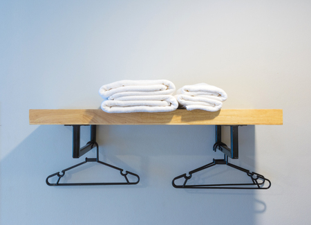 towel prepared on wood shelf and hanger.