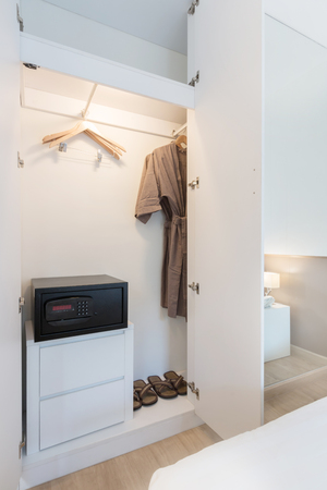 white wardrobe with safe, robe and sandal.