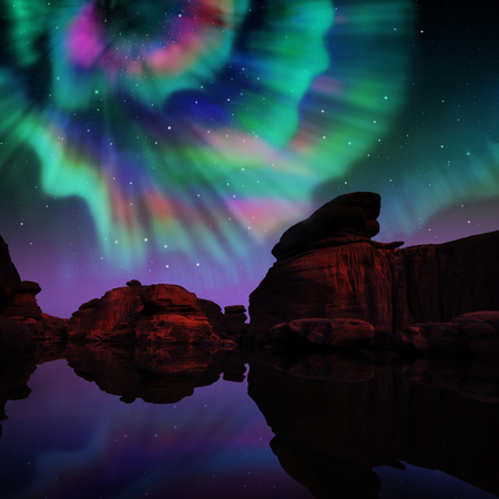 Multicolor aurora over lagoon and red rock. Standard-Bild