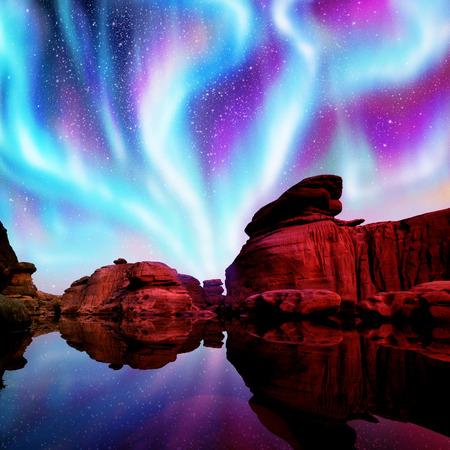 Multicolor Aurora über Lagune und roten Felsen. Standard-Bild