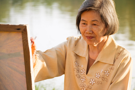 76 years old woman happy with painting in the park.