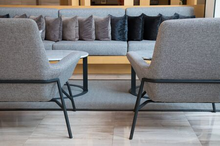 Lobby lounge with grey long sofa, armchairs and round tables on grey carpet in modern residential building. Reklamní fotografie