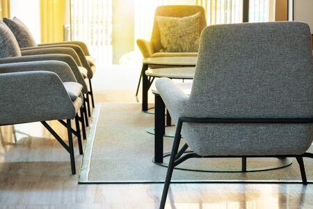 Morning light in lobby lounge with grey armchairs and round tables on grey carpet in modern residential building. Reklamní fotografie