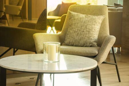 Morning light in lobby lounge with grey armchairs and round tables in modern residential building.