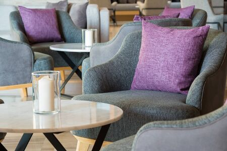 Lobby lounge with grey larmchairs and round tables in modern residential building.