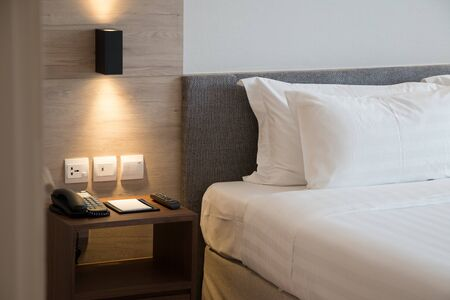 Modern interior hotel bed room with simply soft headbord and telephone ,tv remote on side table. Banco de Imagens