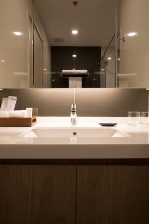 white sink in white mable countertop in luxury hotel restroom.