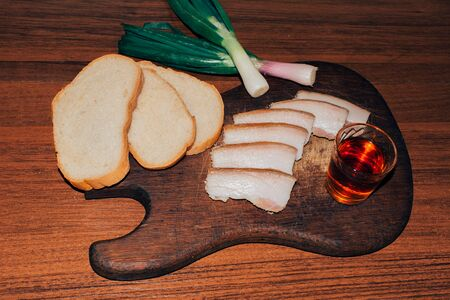 Ukrainian pork lard white bread onion and a glass of alcohol on a wooden surface