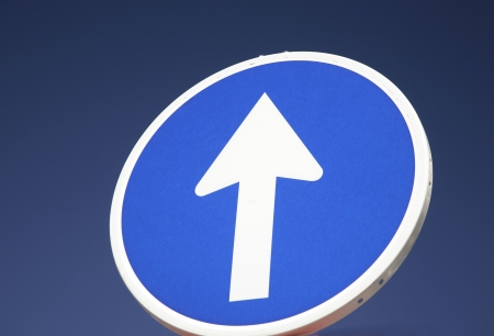 Close-up of a round blue road sign with a white arrow, indicating a one-way street, against a blue sky. Horizontal shot. photo