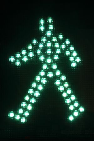 A green traffic light figure on a black background indicating it is safe to walk across the street. Vertical shot. photo